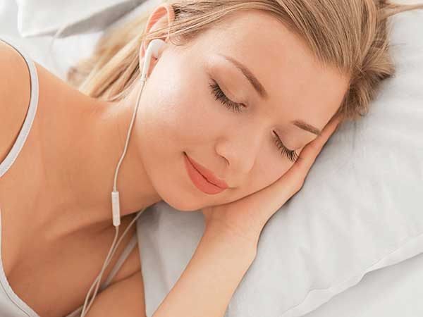 Woman listening to music while falling asleep.