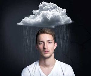 Irritated, depressed man under rain cloud suffering from side effects of insomnia