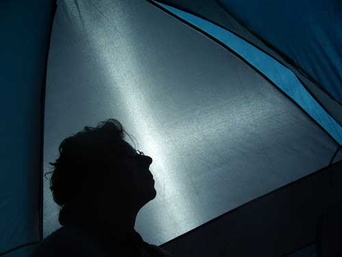Head of person sillouetted inside tent