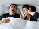Woman suffering from her partner snoring in bed.