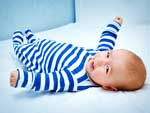 Cute little baby in bed wearing blue and white striped onesie.