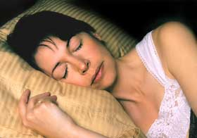 Lady sleeping with head on pillow