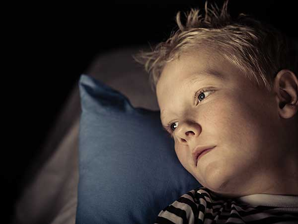 Little boy with childhood insomnia laying on pillow.