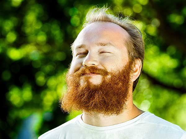 Photo for How To Sleep Better Article featuring man with red beard getting sunshine outdoors.