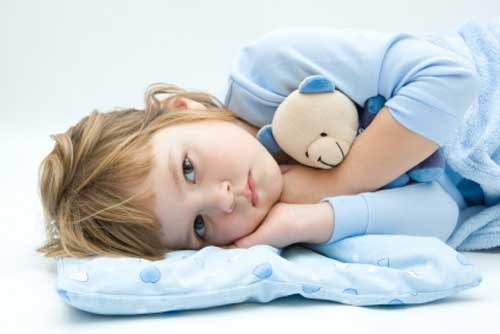 Child laying down hugging teddy bear.