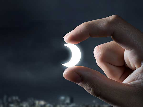 Photo illustration of moon between fingers.