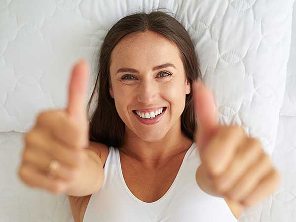 Lady laying on bed give two thumbs up.