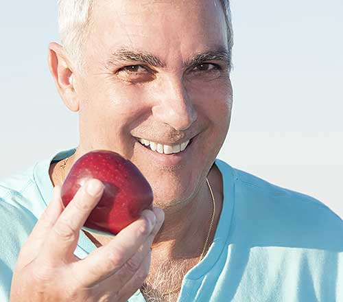 Mature man holding red apple