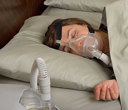 Lady with obstructive sleep apnea wearing CPAP mask