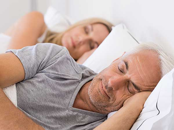 Mature man and woman sleeping.
