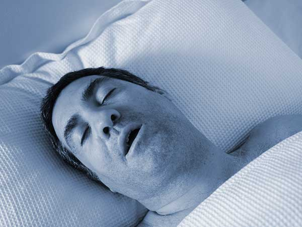 Man with sleep apnea and diabetes laying on back snoring.