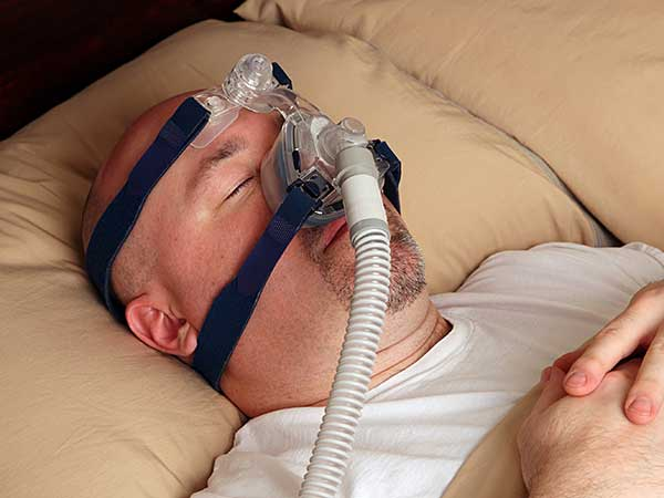 Man sleeping on back using sleep apnea equipment.