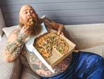 Overweight man eating pizza.