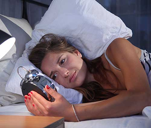 Woman with sleep manintenance insomnia looking at alarm clock