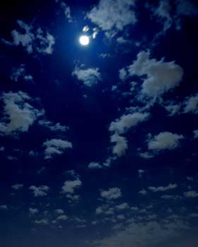 Full moon againt a dark blue cloudy sky.