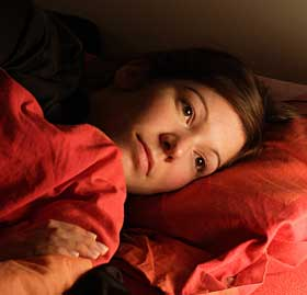 Lady with red blankets laying in bed with eyes open.