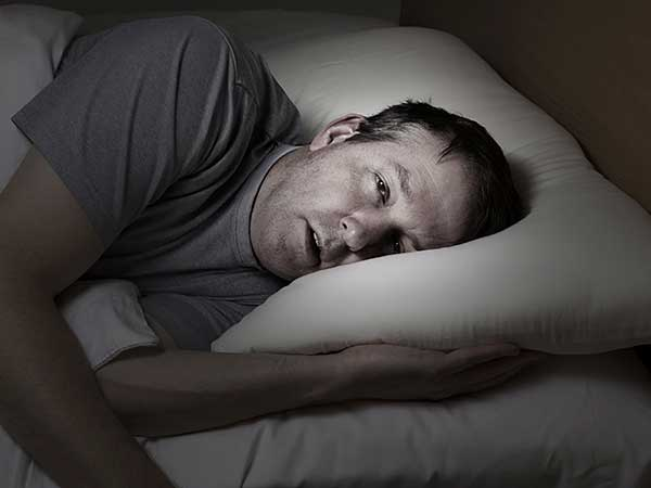 Man laying head on a pillow, unable to sleep.