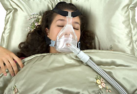 Woman sleeping with Cpap mask on.