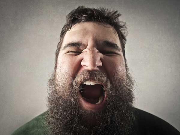 Overweight bearded man yawning.