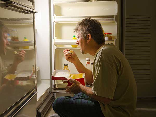 Man with sleep eating disorder eating at night in front of refrigerator.