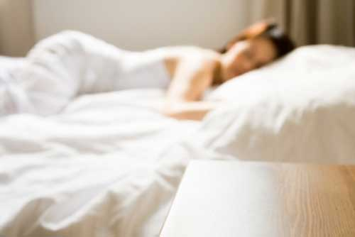 Blurred image of woman laying on mattress